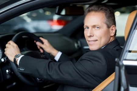 I love this car. Side view of cheerful senior man in formalwear sitting in car and looking over shoulder Stock Photo