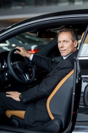 sitting people: I love my new car. Side view of confident senior man in formalwear sitting in car and smiling at camera Stock Photo