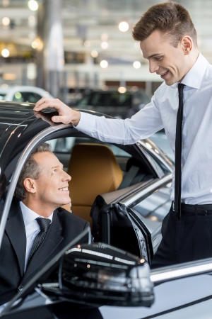 Let me show you all the features. Confident mature man ion formalwear sitting at the front seat of the car and talking to the car salesman standing near him
