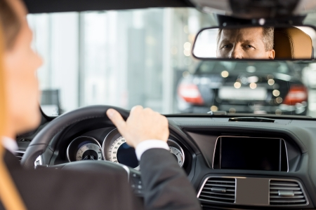 그의 새 차 자신감을 느낌. 드라이버에 앉아 정장에 자신감 수석 남자의 후면보기 자동차에 배치하고 거울을보고