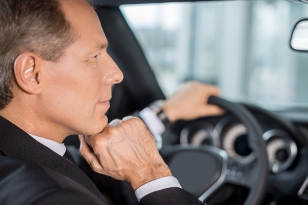 Confident and successful. Confident mature man in formalwear sitting on drivers place in car and looking away photo
