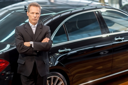 高級車が大好きです。正装車で傾いているとカメラ目線で確信している灰色の髪男のトップ ビュー 写真素材