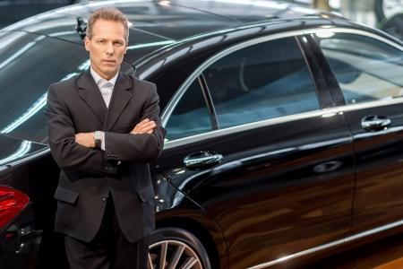 Ik hou van luxe auto's. Bovenaanzicht van overtuigd grijs haar man in formalwear leunend op de auto en kijken naar de camera Stockfoto