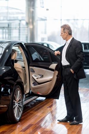 işadamları: Bayiinde araba incelenmesi. Bayiinde arabanın kapısını açarak formalwear güvenen olgun adam tam uzunlukta Stok Fotoğraf