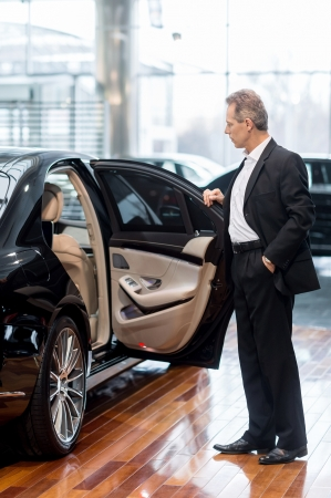 dealership: Examining car at dealership. Full length of confident mature man in formalwear opening the car door at the dealership