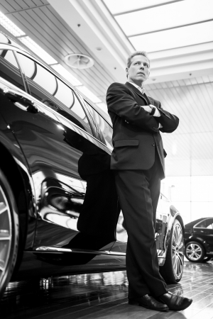 Only luxury cars. Black and white image of full length confident grey hair man in formalwear leaning at the car and looking away