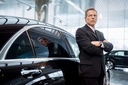 Dreaming of a new car. Thoughtful grey hair man in formalwear leaning at the car and looking away photo