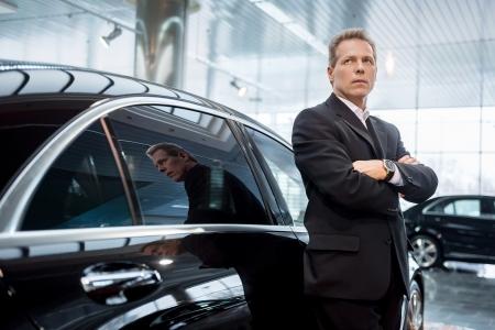 Vous rêvez d'une nouvelle voiture. Cheveux réfléchie homme gris en tenues de soirée se penchant sur la voiture et regarde au loin Banque d'images - 25272238
