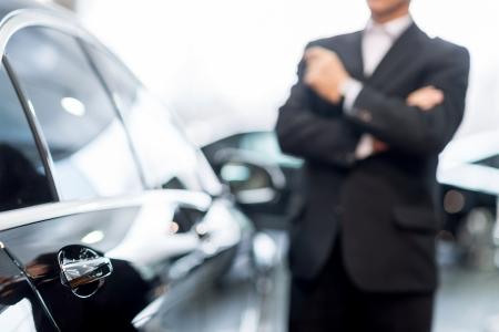 Choisir une voiture chez un concessionnaire. Cheveux gris homme pensif dans de soirée se penchant sur la voiture et regarde au loin Banque d'images - 25272240