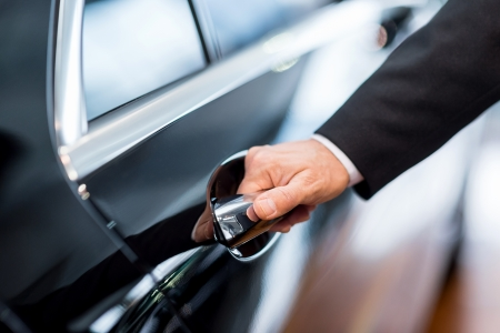 door handle: Hand on handle. Close-up of man in formalwear opening a car door  Stock Photo