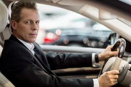 mature businessman: Confident drive. Side view of confident senior man in formalwear sitting in car and looking at camera Stock Photo