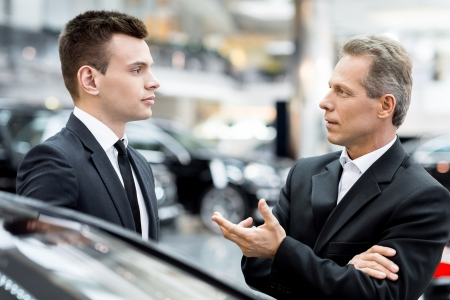 Discussing car features. Two people in formalwear talking to each other and gesturing while standing at the dealership photo