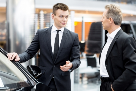Let me show you interior of this car. Handsome young classic car salesman standing in the dealership and helping a client to make a decision about car Stock Photo - 25272191