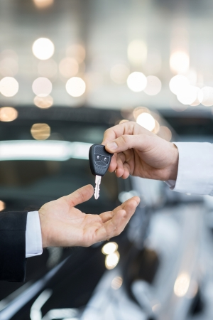 car sales: Here is your key! Close up of man giving key to the car owner while standing in front of a car