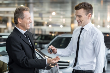 brand new: Giving a key of a brand new car. Handsome young classic car salesman giving a car key to the owner and smiling Stock Photo