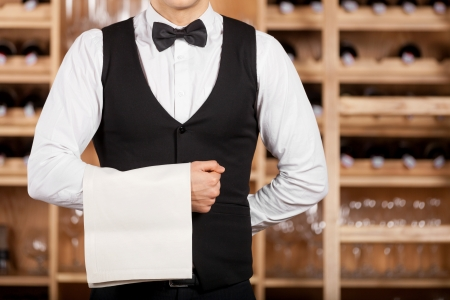 uniform attire: Confident waiter  Cropped image of confident young waiter standing in front of wine shelf and holding a towel on his hand