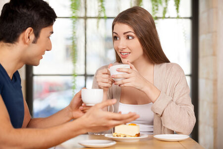 Couple at the restaurant. Beautiful young couple sitting together at the restaurant and drinking coffee photo