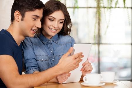 net surfing: Navigare in rete insieme. Bella coppia di giovani seduti insieme al ristorante e con tavoletta digitale Archivio Fotografico