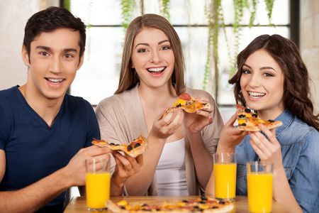 Friends eating pizza. Three cheerful young people eating pizza and smiling at camera while sitting together at the restaurant photo
