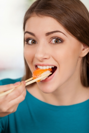 Nigiri is my favorite. Beautiful young woman eating sushi and smiling while sitting at the restaurant photo
