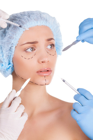 Scared young woman keeping looking away while four hands in medical gloves holding syringes and knifes close to her face photo