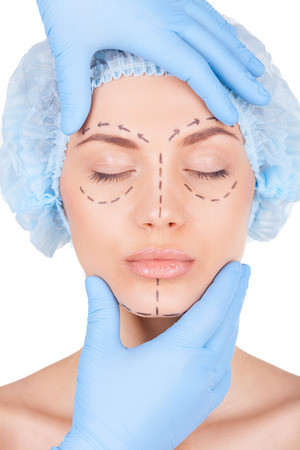 Attractive young woman in medical headwear and sketches on face keeping eyes closed while doctor examining her face isolated on white Stock Photo