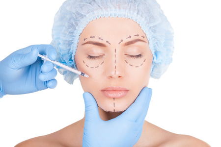 botox: Beautiful young shirtless woman in medical headwear and sketches on face keeping eyes closed while doctors hand making an injection in face