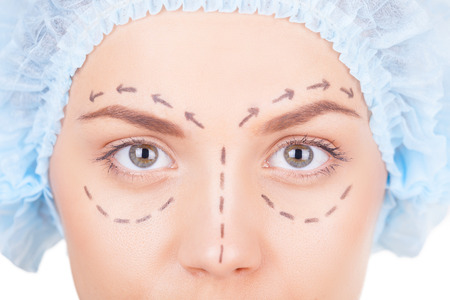 cropped image: Waiting for plastic surgery. Cropped image of beautiful young woman in medical headwear and sketches on face looking at camera while isolated on white