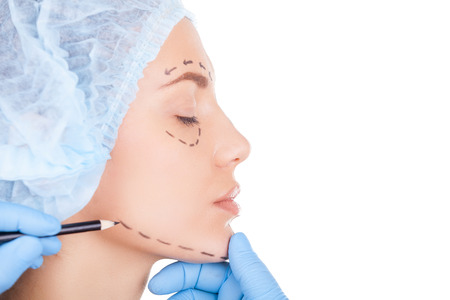 Side view of beautiful young woman in medical head wear keeping eyes closed while doctor sketching her face isolated on white photo
