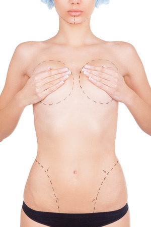 Ready for body improvement. Cropped image of beautiful young shirtless woman with sketches on her body covering her breasts with hands while standing isolated on white background photo