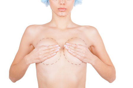 Ready for plastic surgery. Cropped image of beautiful young shirtless woman with sketches on her body covering her breasts with hands while standing isolated on white background photo