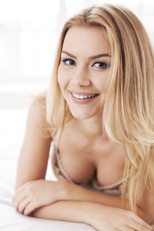 Confident in her beauty. Beautiful young blond hair woman in lingerie lying in bed and smiling at camera photo