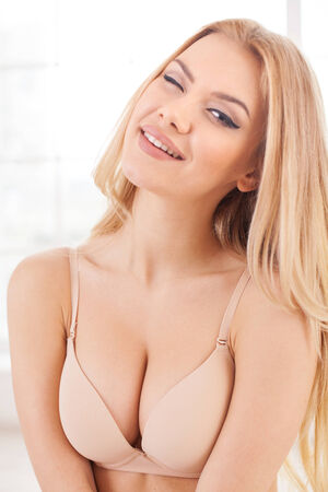 Surprised beauty. Beautiful young blond hair woman in lingerie winking and looking at camera photo