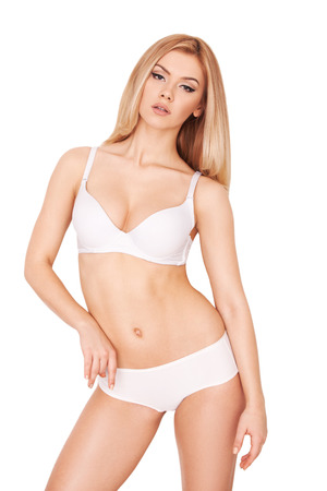 Gorgeous blonde posing. Attractive young blond hair woman in white bra and panties posing against white background   photo