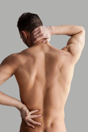 Feeling pain. Rear view of young muscular man touching his back while standing isolated on grey background  photo