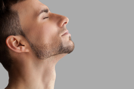 face side: Handsome beard man. Side view of handsome young beard man keeping eyes closed while standing isolated on grey background Stock Photo