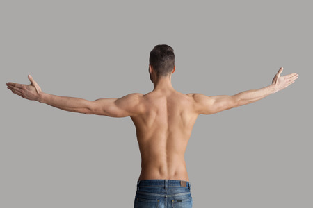 nude back: Man in perfect shape. Rear view of young muscular man keeping arms outstretched while standing isolated on grey background Stock Photo