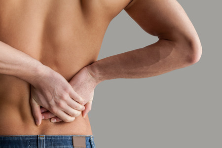 Feeling pain in back. Cropped image of young muscular man touching his back while standing isolated on grey background photo