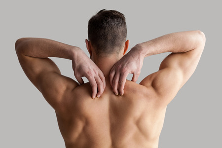 Muscular man. Rear view of young muscular man touching his shoulders while standing isolated on grey background photo