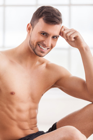 Strong and confident. Handsome young muscular man smiling at camera and holding head in hand photo