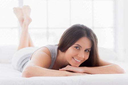 What a pleasure to do nothing! Attractive young smiling woman lying in bed and looking at camera photo