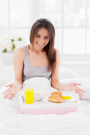 Is this all for me? Surprised young woman looking at the tray with breakfast on it and smiling while sitting in bed and covered with blanket photo