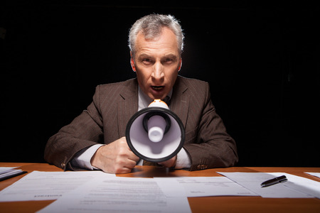 businessman using a megaphone: Furious senior man in formal wear sitting at his working place and shouting at megaphone while isolated on black background  Stock Photo