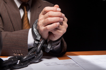 Close-up of man in formal wear with chain on hands sitting at the table and isolated on black background photo