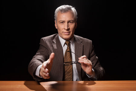 Cheerful senior man in formal wear sitting at his working place and stretching out his hand for shaking while isolated on black background  photo