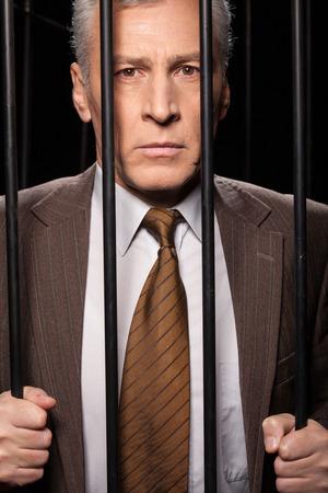 cella carcere: Frustrato uomo anziano in abbigliamento formale in piedi dietro una cella di prigione e guardando la fotocamera mentre isolato su sfondo nero