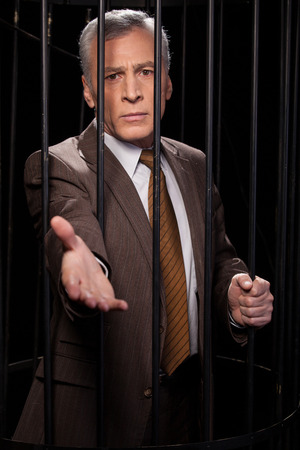 Frustrated senior man in formal wear standing behind a prison cell and stretching out hand while isolated on black background  photo