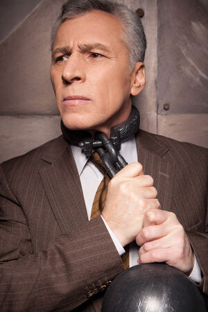 Grey hair senior man in formal wear trying to take off the chain from his neck photo