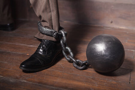businessman leg with metal shackles photo