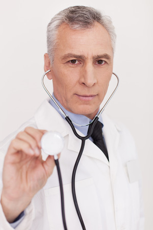 grey hair: Senior grey hair doctor in uniform looking at camera and holding his stethoscope outstretched while standing isolated on white 스톡 사진